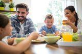 Familienleben: Familie sitzt zusammen am Essenstisch