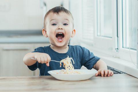 Kinderernährung: Kleiner Junge isst Spaghetti