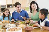 Erziehung: Familie beim gemeinsamen Essen