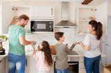 Erziehung: Familie räumt zusammen das Geschirr ein