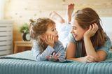 Erziehung: Mutter und Tochter plaudern auf Bett