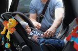 Vater: Schnallt Kind auf Rücksitz an