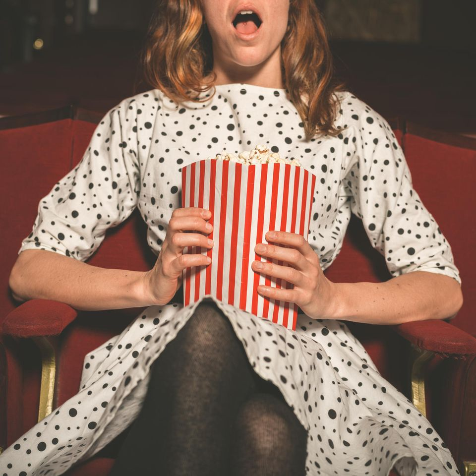 Liebeskomödien: Frau sitzt im Kino mit. Popcorn