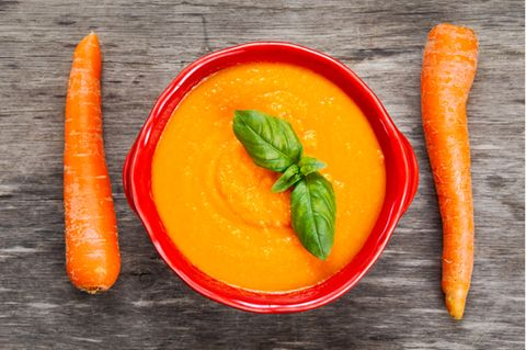 Morosche Karottensuppe: Schüssel mit Karottensuppe und zwei Möhren