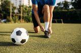 Weniger Worte, mehr Kitzeleinheiten: Mann schnürt Fußballschuh