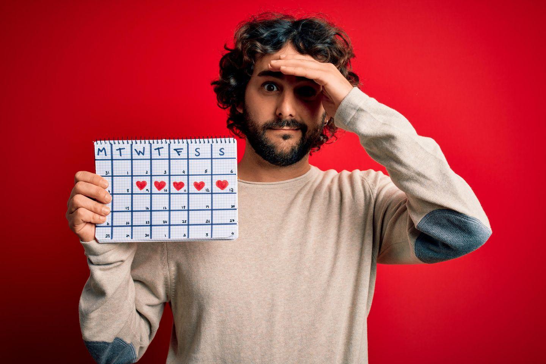 Menstruation: Mann hält ZyklusKalender in der Hand