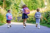 Günstig lernen: Schulkinder von hinten mit Rucksäcken