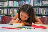 Günstig lernen: Mädchen schreibt Namen auf Schulbuch