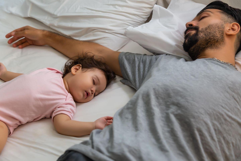 Elternzeit: Vater schläft neben kleinem Mädchen