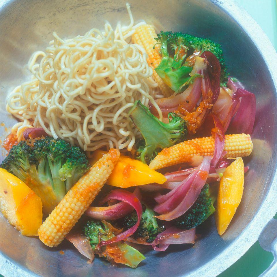 Gemüse und Mango aus dem Wok mit Nudeln und Möhrensoße