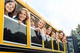 Günstig lernen: Kinder schauen aus Schulbus heraus