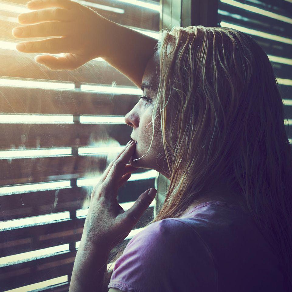 Entropie: Eine Frau steht am Fenster und denkt nach