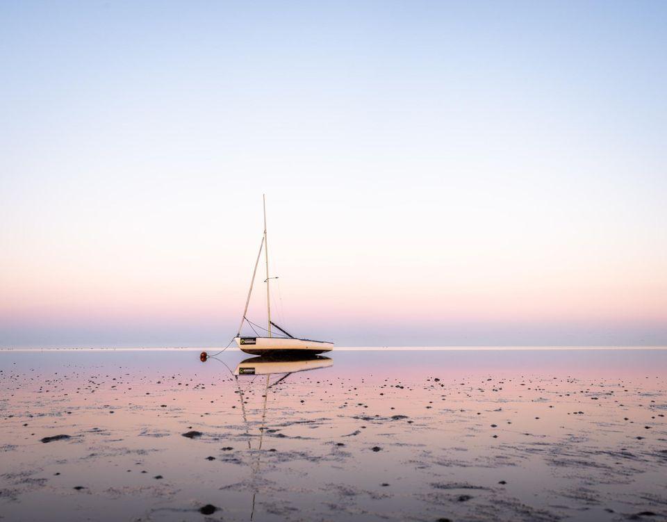 Segelboot bei Ebbe am Strand