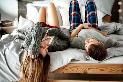 Was sollte sich in der Beziehung leicht anfühlen? Ein Paar liegt auf dem Bett und redet