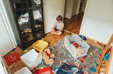 Muttersein: Kind spielt im unaufgeräumten Wohnzimmer