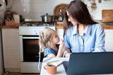 Muttersein: Frau ist mit Kind im Home Office
