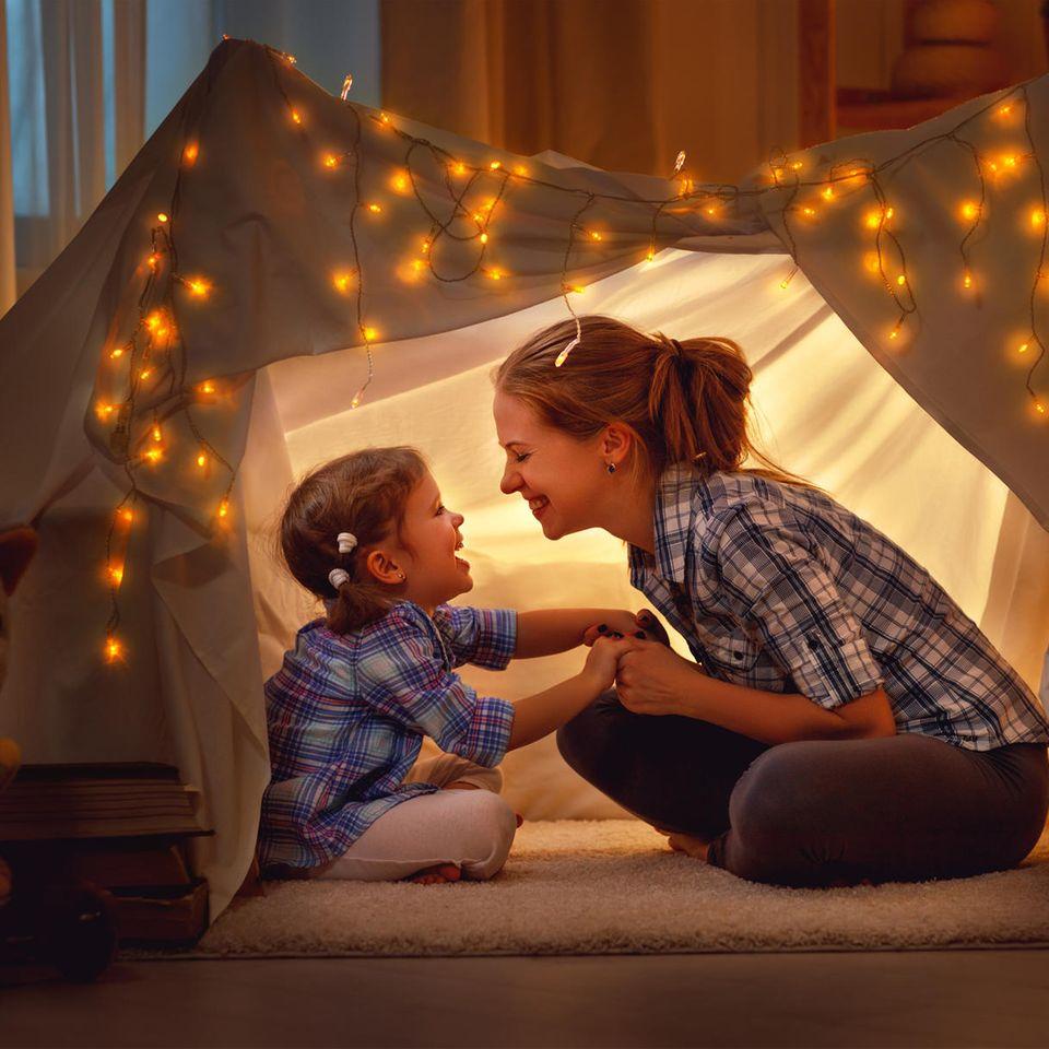 Muttersein: Mutter und Kind spielen  im Zelt