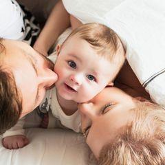 Muttersein: Familie liegt im Bett