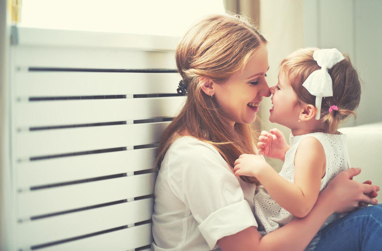 Baby: Mutter kuschelt mit Tochter