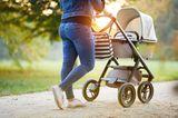 Baby: Frau schiebt Kinderwagen
