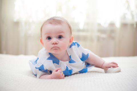 Baby: Baby krabbelt im Bett