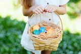 Baby: Kind mit Osterkorb in der Hand