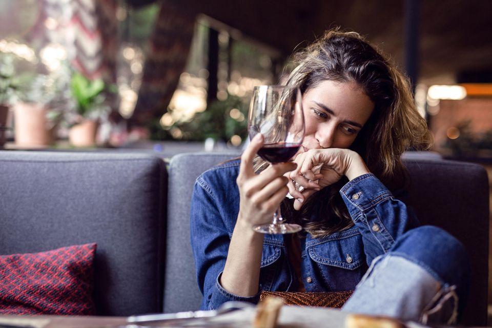 Whisper: Eine Frau amüsiert sich mit einem Glas Wein