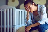 Emotionen im Wochenbett: Erschöpfte Mutter vor Kinderbett