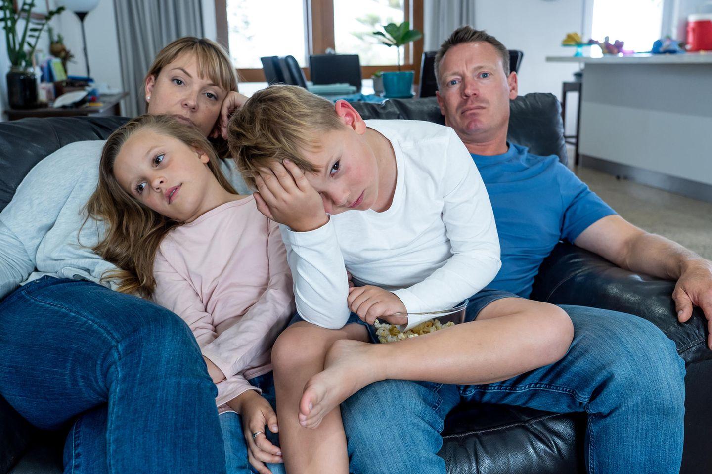 Familienleben: Familie sitzt genervt auf dem Sof