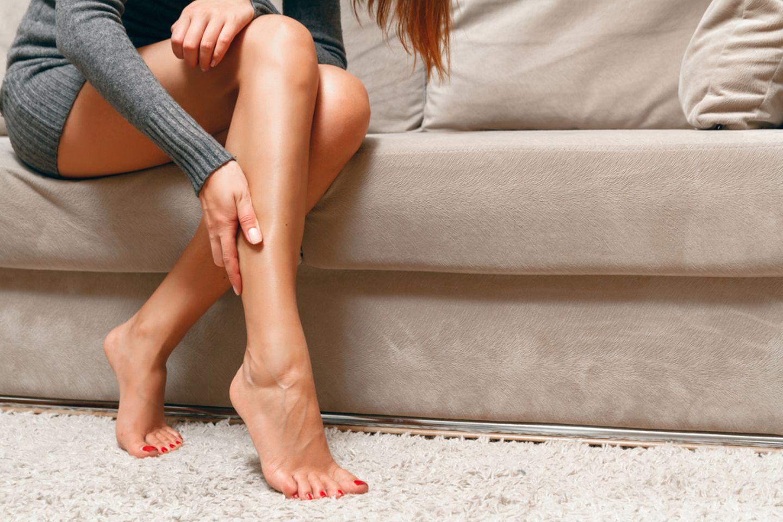 Wadenkrampf: Frau hält sich die Wade