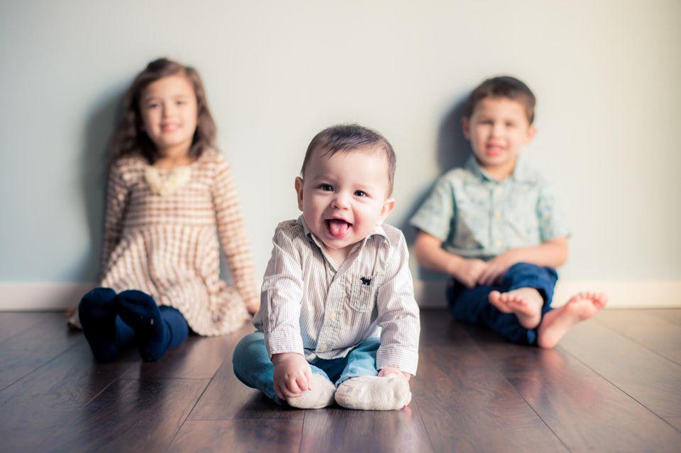 Drittes Kind: Drei Geschwister sitzen auf dem Boden