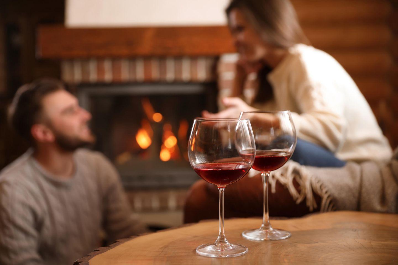 Partnerschaft: Paar vor Kamin mit zwei Weingläsern