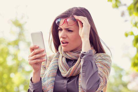 Familienleben: Frau blickt geschockt auf ihr Smartphone