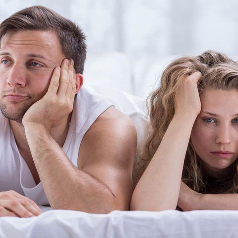 Partnerschaft: Paar liegt genervt im Bett
