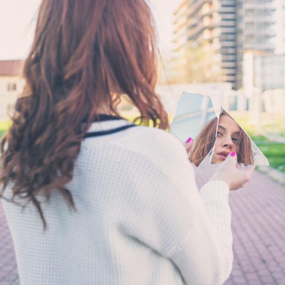Drei Gesichter des Menschen: Eine Frau schaut in einen zerbrochenen Spiegel