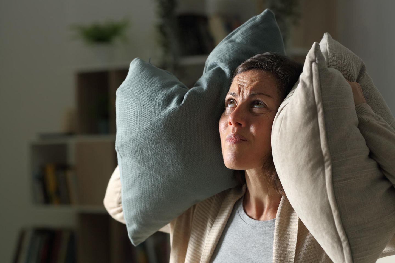 Depression: Frau hält sich mit Kissen die Ohren zu
