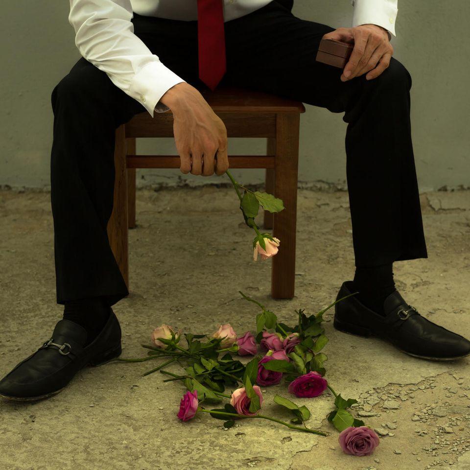 Reddit: Ein trauriger Mann mit zerfallenden Blumen und Ringschatulle