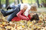 Baby: Mutter und Kind spielen in Herbstblätter