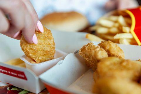Maske in Chicken Nuggets: Frau isst Chicken Nuggets