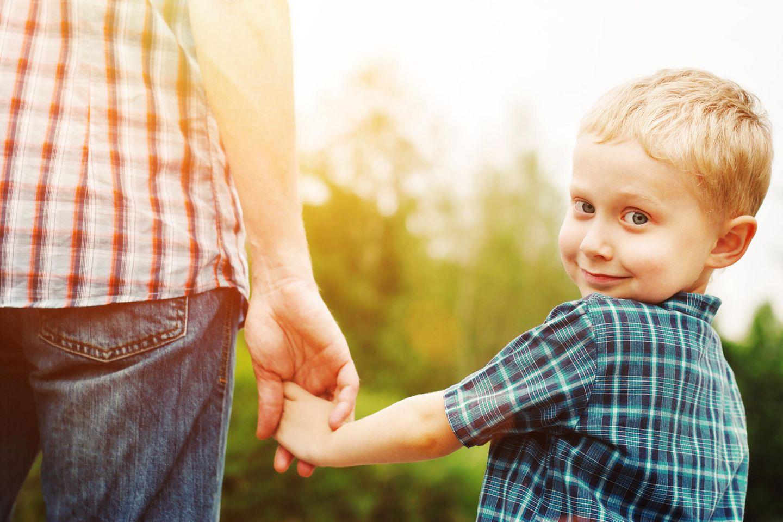 Vater nimmt Kind an die Hand