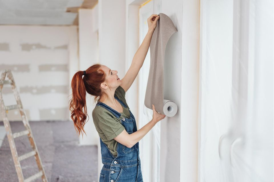 Frau hält Tapete an Wand