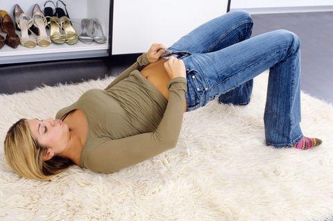 Hose anprobieren: Frau steht verzweifelt in der Umkleide