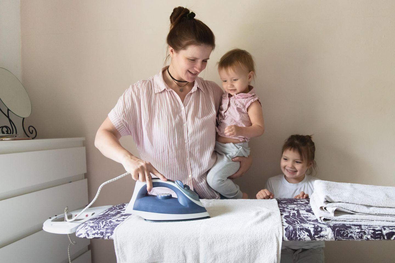 Familienleben: Frau mit zwei Kindern am Bügelbrett