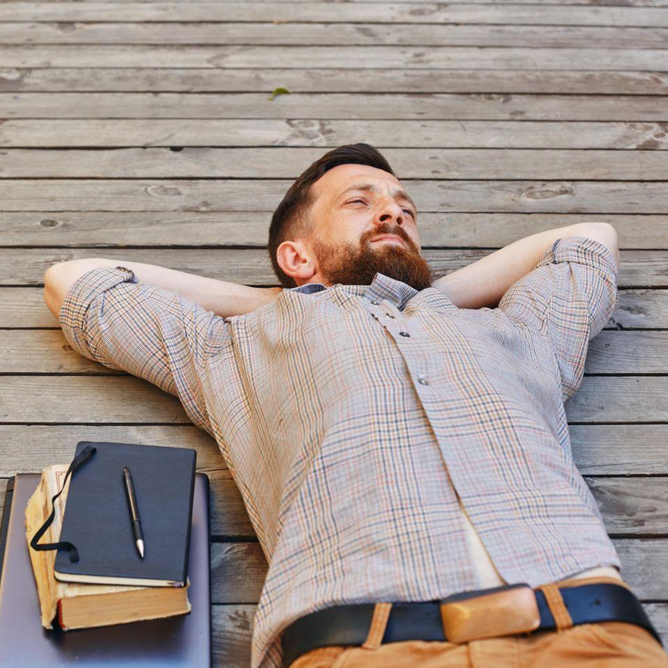 Was Männer nach einer Trennung bereuen: Ein Mann liegt auf dem Rücken und denkt nach