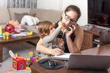 Familienleben: Gestresste Mutter am Computer