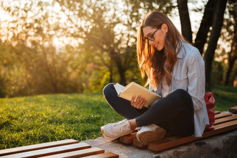 Familienleben: Frau liest draußen auf Bank