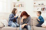 Kindern Grenzen setzen: Mutter sitzt zwischen streitenden Kindern
