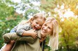 Kindern Grenzen setzen: Mutter trägt Tochter Huckepack