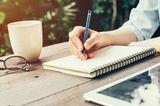Mama-Krise: Frau schreibt in ihr Notizbuch