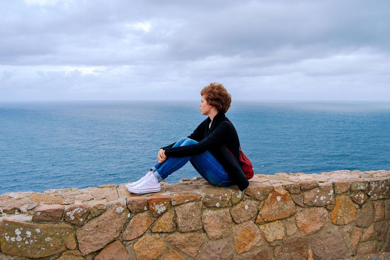 Wann sollte ich auf mein Bauchgefühl hören? Eine Frau mit Locken sitzt am Meer und denkt nach